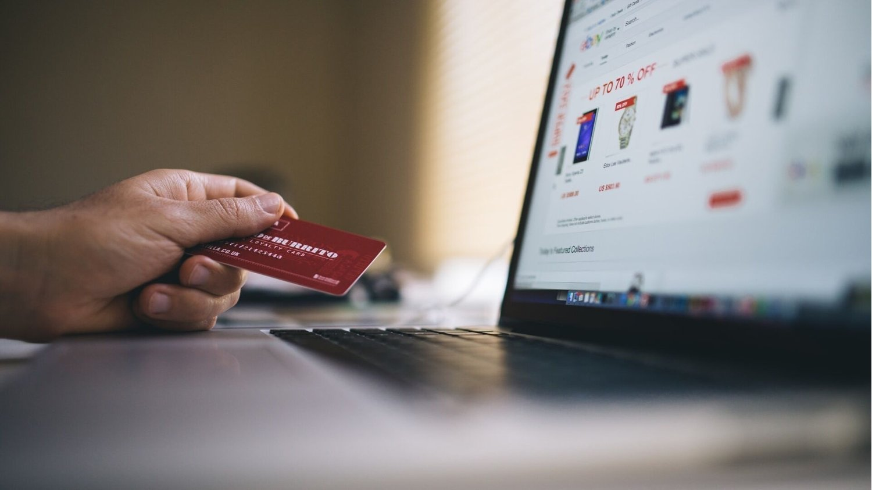 Person zückt Kreditkarte am Laptop während des Onlineshoppens am Black Friday
